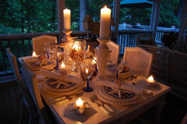 Romantic dinner table setting with burning candles